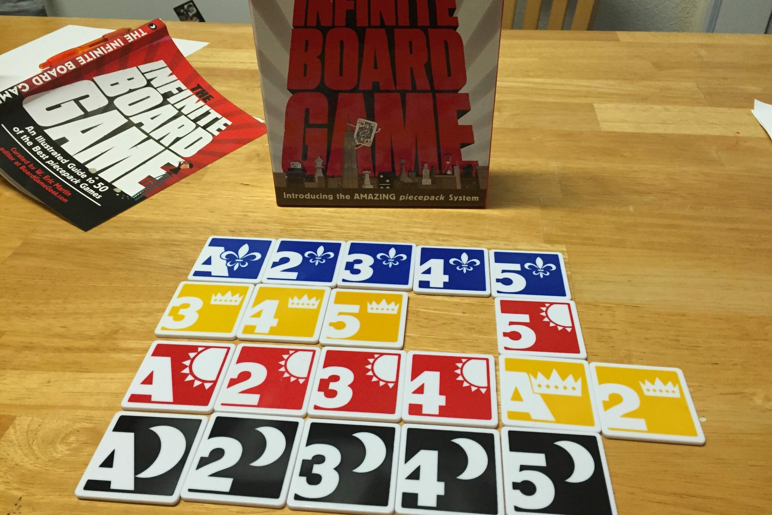 Several tiles from the Infinite Board Game: square white plastic tiles with rounded corners and a bold design.